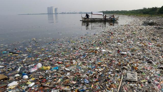Müll schwimmt am Strand, im Hintergrund ein Boot und noch weiter hinten Hochhäuser.