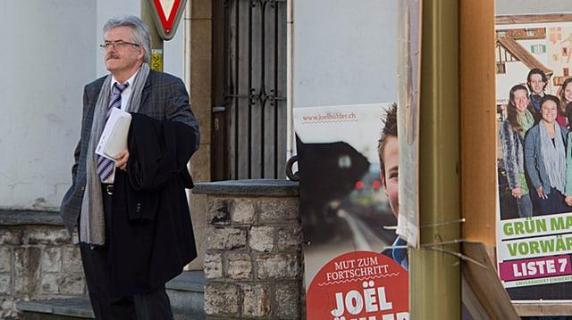 Oskar Kämpfer steht neben verschiedenen Wahlplakaten und schaut in die Ferne.