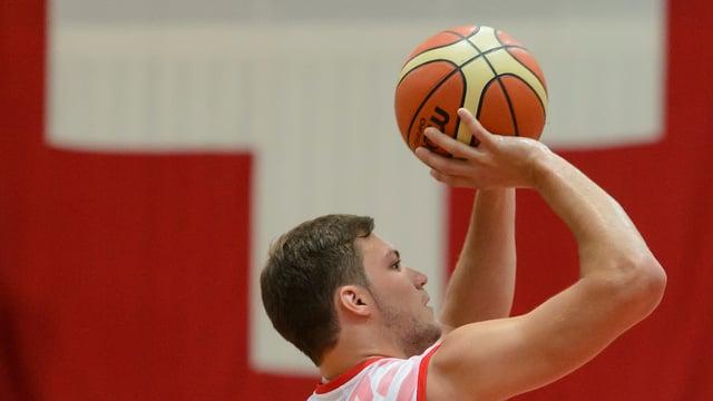 Ein Schweizer Basketballer wirft einen Ball vor einer Schweizer Flagge.