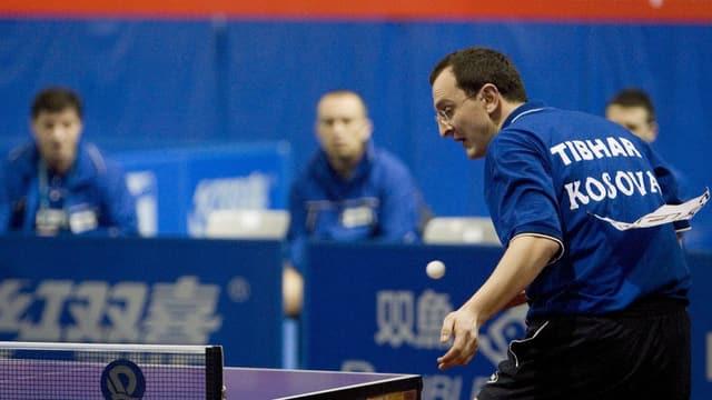 Symbolbild: Kosovarischer Tischtennis-Spieler mit Brille und blauem Shirt mitten in einem Match.