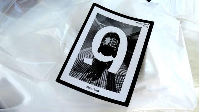 Das Magazin Delirium liegt auf einer zerknitterten Plastiktüte.