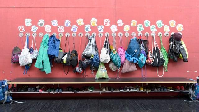 Eine Garderobe in einem Primarschulhaus, mit vielen Turnbeuteln und Schuhen.