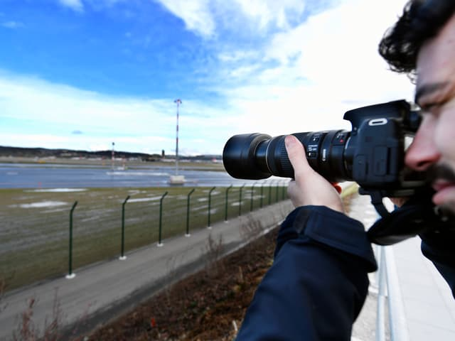 Mann mit Fotokamera mit grossem Objektiv.