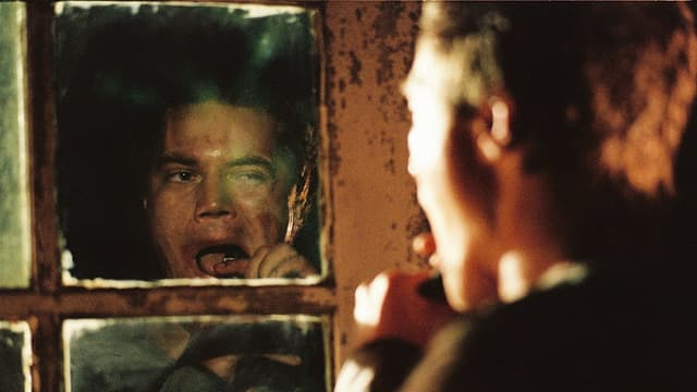 Ein Mann puhlt vor dem Spiegel ein Stück Metall aus seinem Mund.