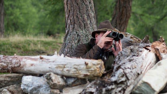 Ein Jäger blickt durch sein Fernglas.