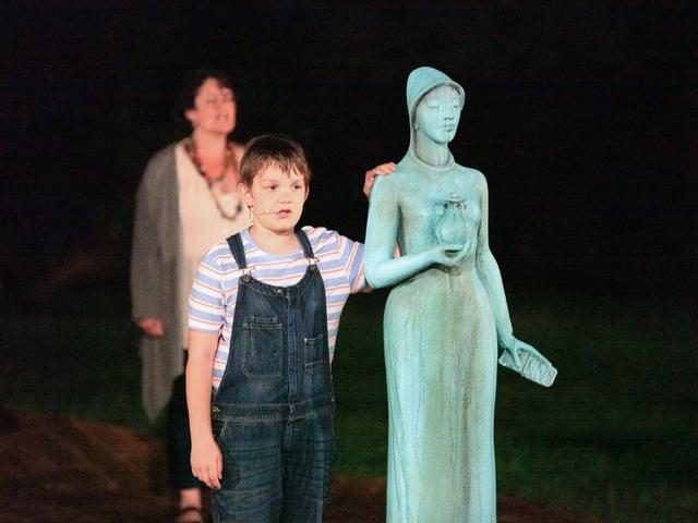 Ein Knabe hat seine Hand auf eine weibliche Statue gelegt.