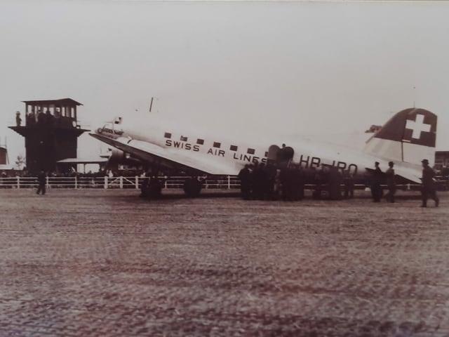 Auf einem historischen Foto steht das Flugzeug DC3 vor einem Kontrollturm.