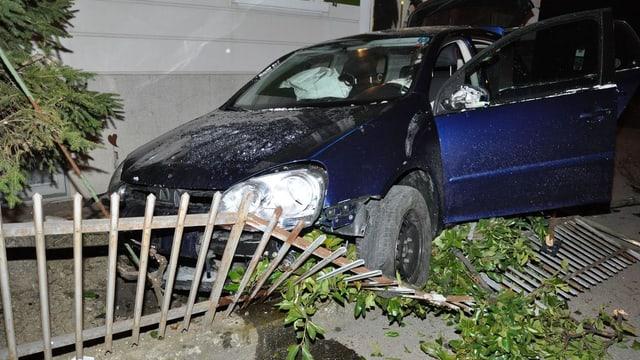 Das Wrach eines Autos, welches einen Zaun und einen Baum gerammt hat.