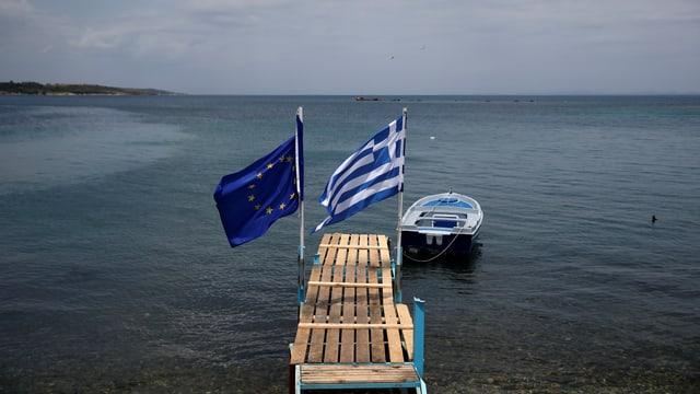 Ein Holzsteg im Meer mit einer EU- und einer griechischen Fahne.