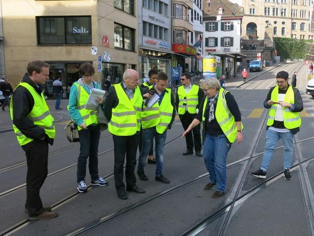 Acht Personen in gelben Schutzwesten schauen sich die Tramgleise am Boden an.