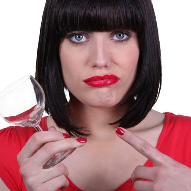 Frau mit roten Lippen zeigt frustriert auf ein Glas.