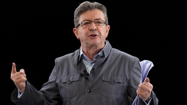 Jean-Luc Mélenchon redet auf einer Bühne mit Papieren in der linken Hand.