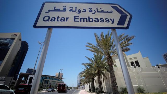 Ein Wegweiser zur Botschaft von Katar in Bahrain vor einer mit Palmen gesäumten Strasse.