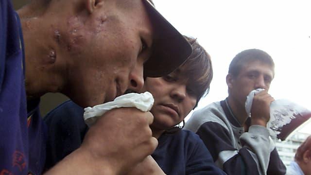 Drei mit Narben übersähte Jugendliche halten Plastiksäcke an den Mund.