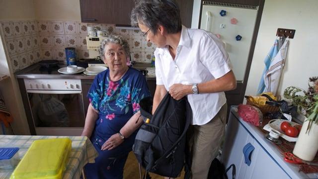 Eine jüngere Frau hilft einer älteren.