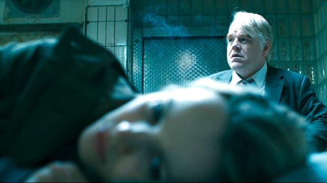 Im Vordergrund ist der Kopf einer liegenden jungen Frau sichtbar, hinter ihr sitzt ein älterer Mann in Anzug und Krawatte. Der Raum ist ganz in grünes Licht getaucht.