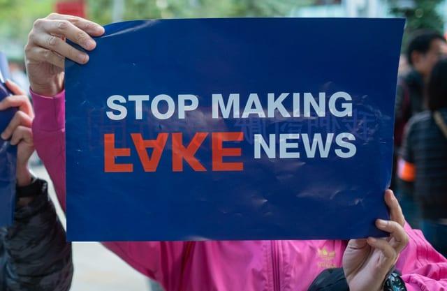 """Zwei Hände halten ein """"Stop Making Fake News""""-Schild in die Luft."""