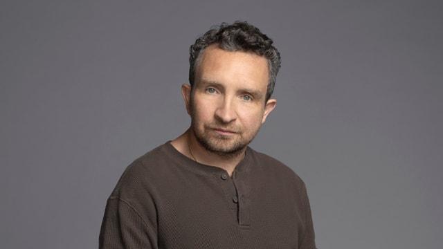 Ein Mann mit grau meliertem Haar und dunklem Pullover.