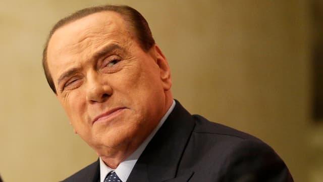 Berlusconi blickt mit einem Auge geschlossen zur Seite.