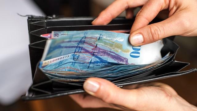 Eine Person greift in ein Portemonnaie