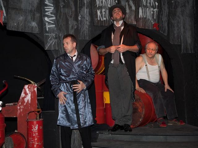 Drei Männer stehen auf einer Bühne.
