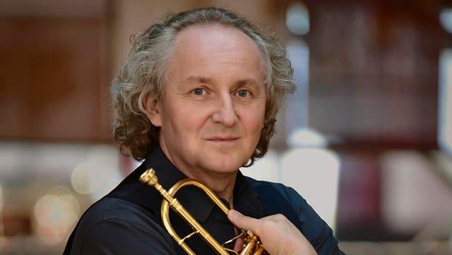 Alter hübscher Mann umarmt seine Trompete und lächelt leicht.