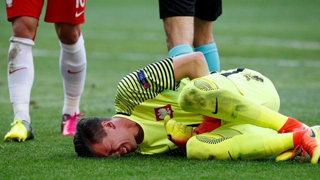 Wojciech Szczesny wälzt sich mit schmerzverzerrtem Gesicht auf dem Rasen.