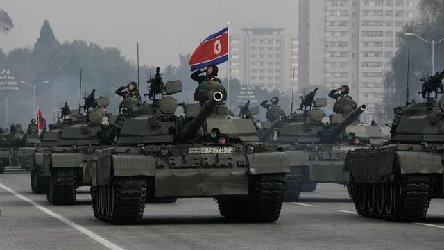 Panzer mit Soldat auf einer Militärparade in Nordkorea. Im Hintergrund die nordkoreanische Flagge.