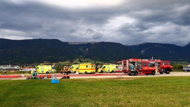 Ambulanzen und Feuerwehrfahrzeuge auf dem Rollfeld, im Hintergrund Jura-Kette