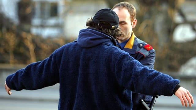 Mann von hinten mit ausgestreckten Armen, Polizist