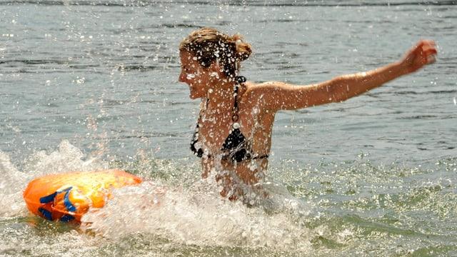 Eine Frau springt in Rhein bei Basel. Das Wasser spritzt.