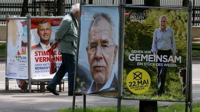 Ein Mann marschiert zwischen Wahlplakaten hindurch.