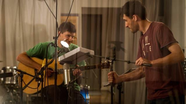 Ein junger Mann mit Gitarre sitzt in einem Tonstudio, ein zweiter junger Mann hält das Mikrofon.