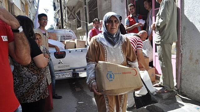 Ein Frau in Syrien trägt eine kleine Kartonschachtel mit Lebensmitteln.