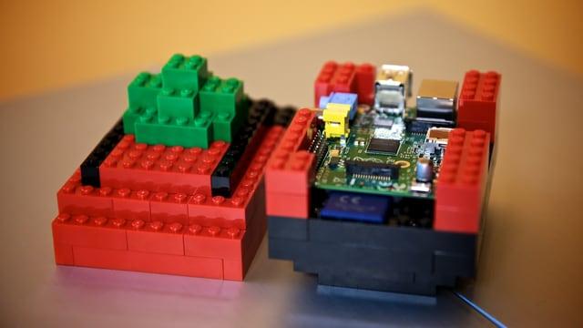 Die Platine des Raspberry Pi sitzt in einem Gehäuse aus roten und schwarzen Legosteinen.