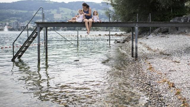 Eine Frau sitzt mit ihren Kindern auf einem Steg am Bodensee.