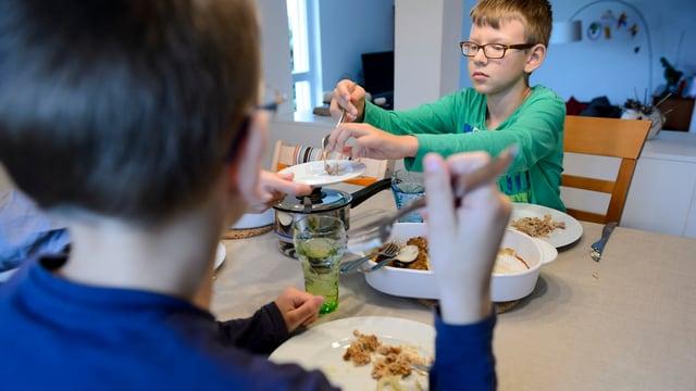 Zwei Kinder sitzen an einem Tisch