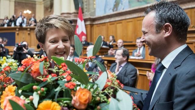 Sommaruga hinter einem Blumenstrauss, zu ihrer Rechten: Nationalratspräsident Stéphane Rossini von der Seite.