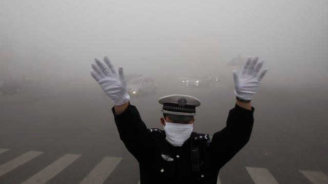 Ein Polizist mit Atemschutzmaske regelt den Verkehr