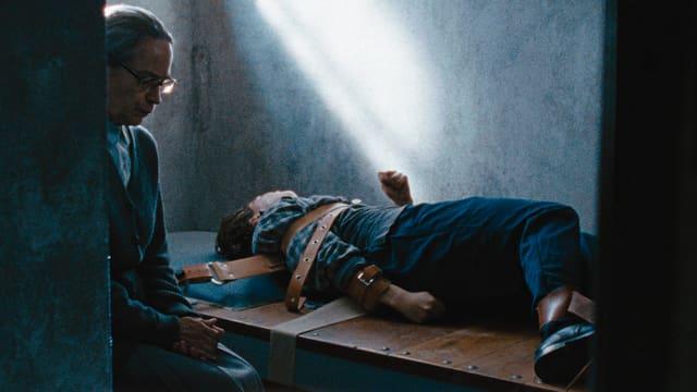 Eine ältere Frau sitzt in gedanken versunken neben einem Bett, auf dem eine jüngere Frau gefesselt liegt und sich windet.