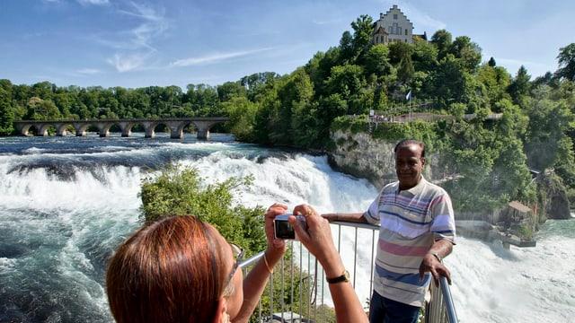 Eine Frau schiesst ein Foto von einem dunkelhäutigen Touristen vor dem Rheinfall.