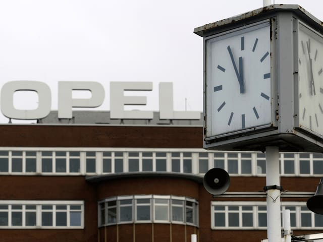 Vor der braunen Fassade des Opel-Werks in Bochum zeigt eine Uhr fünf vor zwölf.