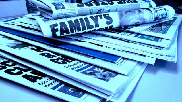 Zeitungen mit englischen Schlagzeilen liegen übereinander.