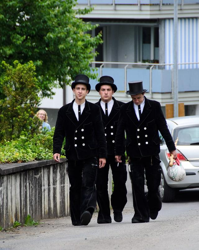 Drei Männer in schwarzen Anzügen und mit Hut.