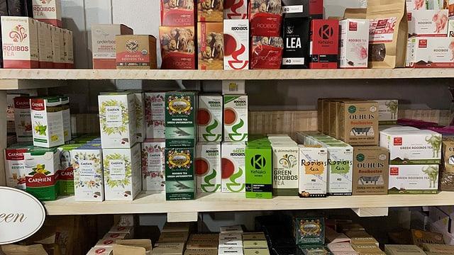 Das Verkaufsgestell eines Ladens, voll mit Produkten aus der Rooibos-Pflanze.