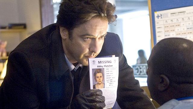 Ein Mann hält einem anderen Mann eine Vermisstenanzeige vors Gesicht.