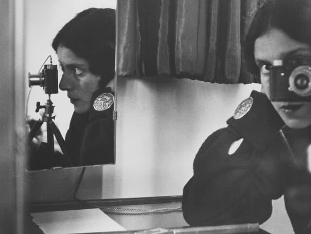 Selbstporträt einer Frau: Man sieht sie durch die Kamera schauen und gleichzeitig einen Spiegel, in dem sich die Fotografin spiegelt.