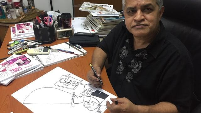 Karikaturist Zunar, vor einer Zeichnung sitzend