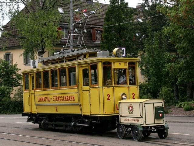 Ein Gelbes Tram mit einem hellbraunen Anhänger fährt durch eine Stadt.
