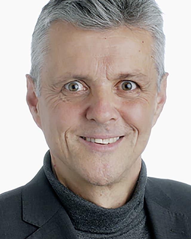 Ein Foto von einem lächelnden Mann mit grauen Haaren und grauem Jackett.